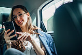 Businesswoman riding on back seat of a car and using smart phone