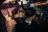 One young hairdresser cutting hair of a male client at barber shop