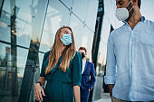 Business people with protective masks walking by the office building