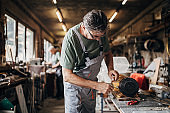 Senior craftman rebuilding an engine in small workshop