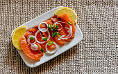 Salted slides of salmon served with slides of lemon and onion