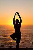 Portrait of athletic senior active woman practicing yoga at the beach with a beautiful sunset.