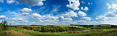 Sunny summer landscape with river,golden fields,green hills and beautiful clouds in blue sky. Extra wide panorama.