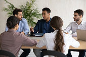 Focused diverse businesspeople brainstorm at office meeting