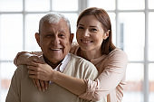 Head shot portrait of smiling young woman cuddling old father.