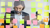 Businessman writing on attached multicolored sticky notes new ideas
