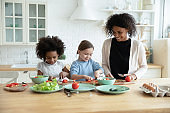 Caring african american mommy teaching little girls cooking.