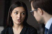 Serious young indian ethnicity businesswoman talking to male confident partner.