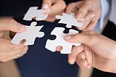 Closeup hands holding white pieces of puzzles find right solution