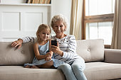 Old granny little granddaughter sitting on couch with smartphone