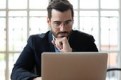 Serious thoughtful businessman wearing glasses looking at laptop screen