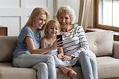 Multi-generational women family sit on sofa using smartphone