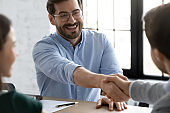 Smiling businessmen handshake closing deal at office meeting