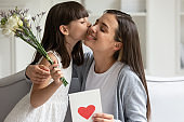 Little daughter congratulate excited young mom presenting flowers