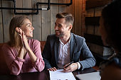 Overjoyed young couple closing deal with realtor in cafe