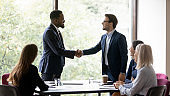 Smiling diverse businessmen handshake closing deal at meeting