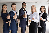 Diverse corporate team businesspeople standing in line showing thumbs up