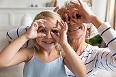 Old grandma little granddaughter making binoculars with fingers like eyeglasses