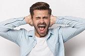 Furious man close ears scream avoiding loud noise
