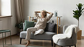 Peaceful satisfied mature woman relaxing on comfortable sofa at home