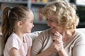 Overjoyed mature grandmother have fun talking with little granddaughter