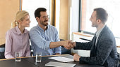 Smiling male financial advisor shaking hands with clients.