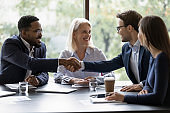 Smiling diverse employees handshake at briefing in office