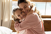 Happy young mom and little daughter hugging at home