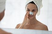 Mirror reflection close up young woman applying anti blackhead patch
