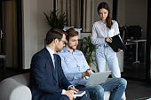 Diverse colleagues work together on laptop at casual meeting