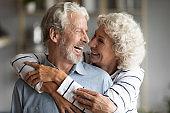 Happy elderly couple hug and cuddle sharing romantic moment
