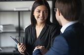 Smiling multiracial business partners handshake greeting at meeting