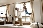 Playful young father lifting little preschool daughter in air.