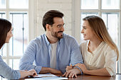 Smiling young couple meeting with female relator in office