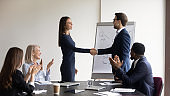 Smiling diverse businesspeople handshake close deal at briefing