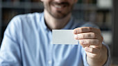 Close up smiling businessman showing blank business card to camera