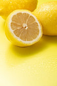 Fresh lemons on a yellow background
