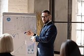 Serious businessman present business project on whiteboard at meeting
