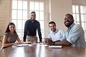 Smiling diverse colleagues look at camera brainstorming at meeting