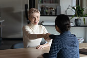 Smiling diverse female colleagues handshake at business meeting