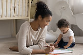 Smiling African American mother and toddler girl drawing colorful pencils