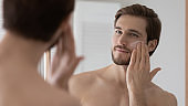Close up mirror reflection handsome young man applying moisturizing cream