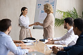 Mature executive shaking Arabic businesswoman hand at corporate meeting