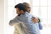African and Caucasian guys hugging glad to see each other