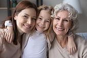 Head shot portrait smiling little girl hugging mother and grandmother