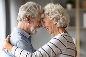 Smiling mature husband and wife share romantic moment together