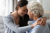 Grownup granddaughter touch foreheads hugs elderly grandmother enjoy tender moment