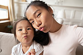 Beautiful mother little daughter taking selfie webcam faces view