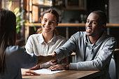 Happy interracial couple handshake bank manager take mortgage loan