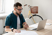 Focused male employee make notes watching webinar